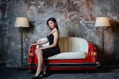 En härlig flicka i en svart klänning sitter på en ovanlig handgjord soffa Soffa från bilsätet arkivfoto