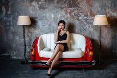 En härlig flicka i en svart klänning sitter på en ovanlig handgjord soffa Soffa från bilsätet royaltyfria foton
