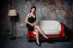 En härlig flicka i en svart klänning sitter på en ovanlig handgjord soffa Soffa från bilsätet arkivbilder