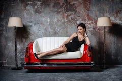 En härlig flicka i en svart klänning sitter på en ovanlig handgjord soffa Soffa från bilsätet royaltyfri foto