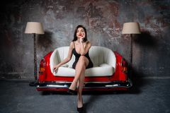 En härlig flicka i en svart klänning sitter på en ovanlig handgjord soffa Soffa från bilsätet royaltyfri fotografi