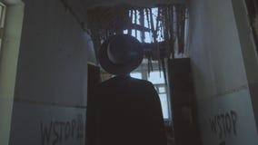 En härlig flicka i svartkläder och en hatt som promenerar ett gammalt kollapsat byggande Flicka i hatt arkivfilmer