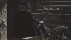 En härlig flicka i svartkläder och en hatt som promenerar ett gammalt kollapsat byggande Flickan i en hatt röker stock video