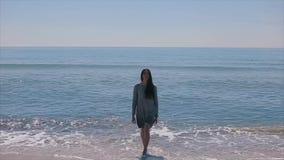 En härlig flicka i en våt kort klänning går ut ur det krabba havet och går in mot kameran arkivfilmer