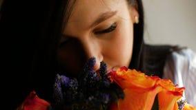 En härlig flicka kommer med en bukett av blommor till hennes näsa och luktar dem som står på fönstret closeup arkivfilmer