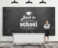 En härlig flicka med den svarta dokumentmappen och lärares skrivbord i en modern skola En svart svart tavla på väggen med skriftl Arkivfoto