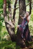En härlig flicka med en fiol i en lång klänning svävar bland träden Arkivfoto
