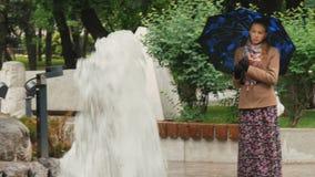 En härlig flicka med ledsna ögon står i regnet i staden parkerar, nära springbrunnen