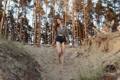En härlig flicka med en longboard i hennes händer i natur i en pinjeskog i sökande av en bra väg som skulle rida royaltyfri foto