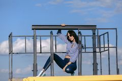En härlig flicka med solglasögon och sönderriven jeans och en randig skjorta Mot bakgrunden av stora stålstrukturer Royaltyfria Foton