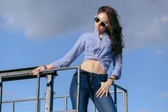 En härlig flicka med solglasögon och sönderriven jeans och en randig skjorta Mot bakgrunden av stora stålstrukturer Royaltyfri Bild