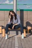 En härlig flicka med solglasögon och sönderriven jeans och en randig skjorta Mot bakgrunden av stora stålstrukturer Konstnärlig p Royaltyfria Foton