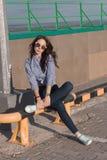 En härlig flicka med solglasögon och sönderriven jeans och en randig skjorta Mot bakgrunden av stora stålstrukturer Konstnärlig p Royaltyfri Foto