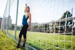 En härlig flicka med stängda ögon i en blå skjorta och damasker står nära ett fotbollmål på stadion på solnedgången härlig sun arkivfoton