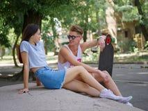 En härlig flicka och en kamrat med ett longboardsammanträde på stentrappa på en naturlig suddig bakgrund arkivbild