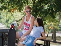 En härlig flicka och en kamrat som talar på en bänk, ett gulligt par av tonår som daterar i en parkera, på ett naturligt suddigt royaltyfria bilder