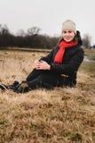 En härlig flicka sitter i ett fält med en hatt och en halsduk arkivbild