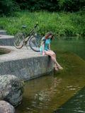 En härlig flicka sitter nära en cykel nära ett damm royaltyfri fotografi