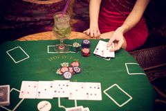 En härlig flicka sitter på en soffa som spelar poker på den gröna torkduken och, rymmer spela kort i hennes händer royaltyfri fotografi