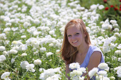 En härlig flicka som ler i ett fält av vita blommor Royaltyfria Foton