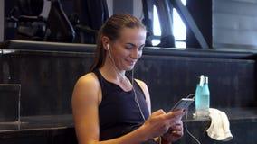 En härlig flicka vänder på musik i hörlurar, innan han gör sportar royaltyfri foto