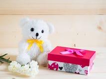 En härlig gåva med den älskvärda björnen och den trevliga vita nejlikan blommar på träbakgrund Royaltyfria Bilder