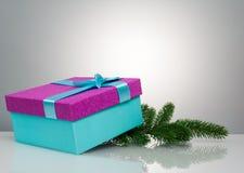 En härlig gåvaask i blått, med ett purpurfärgad band och pilbåge Under den ligger en filial av en julgran härligt royaltyfri fotografi