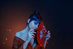 En härlig geisha med blått långt hår och en smäll ser i anda rött smink, kanter, lång klänning med öppna shoders royaltyfria bilder