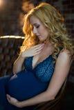 En härlig gravid flicka sitter på soffan i en vindinre Arkivbild