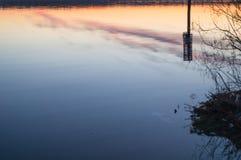 En härlig guld- solnedgång på floden Arkivfoton