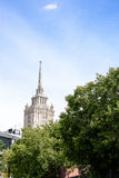 En härlig högväxt byggnad, en Stalin skyskrapa på bakgrunden av en del av byggnaden av det Ukraina hotellet mot blåtten s arkivbild