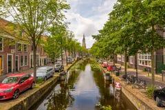 En härlig historisk kanal i mitten av delftfajans, Nederländerna med en sikt på det kyrkliga tornet arkivfoto