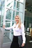 En härlig kontorsdam som öppnar en dörr Arkivfoto