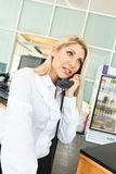En härlig kontorsdam som talar på telefonen med leende Fotografering för Bildbyråer