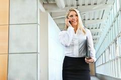 En härlig kontorsdam som talar på telefonen och gå Fotografering för Bildbyråer