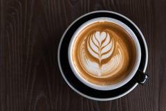 En härlig kopp av Lattekonst på träutrymmebakgrunden Royaltyfri Foto