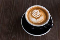 En härlig kopp av Lattekonst på träutrymmebakgrunden Royaltyfri Bild
