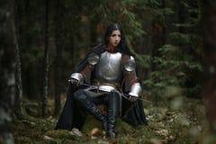 En härlig krigareflicka med en bärande chainmail för svärd och harnesk i en mystisk skog arkivbild