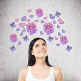 En härlig kvinna drömmer om gåvan Purpurfärgade gåva- och hjärtasymboler dras på betongväggen Royaltyfria Bilder