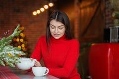 En härlig kvinna dricker te nära en stucken röd tröja Begreppshem, komfort, livsstil, höst, vinter, kafé arkivfoton