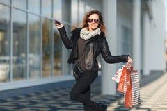 En härlig kvinna går till och med staden på shopping, henne är jätteglad av köp i periodförsäljningarna Begrepp: mode shoppi royaltyfria bilder