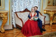 En härlig kvinna i en röd klänning med en man som sitter i en stol, bruden och brudgummen, lyckliga nygifta personer royaltyfria foton