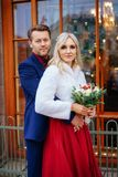 En härlig kvinna i en röd klänning står med en man, en brud och en brudgum, lyckliga nygifta personer arkivfoton