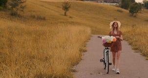 En härlig kvinna med en cykel i en hatt och en ljus sommarklänning kommer med blommor i en korg och leenden lager videofilmer