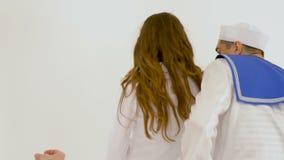 En härlig kvinna med långt hår och två skådespelare i dräkter av sjömän, utför en dans Anteckna ett musiknummer lager videofilmer