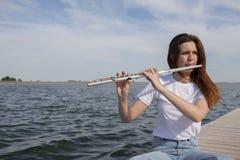 En härlig kvinna som poserar i strand, medan spela på en flöjt royaltyfri foto