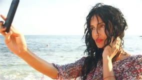 En härlig kvinna tar bilder med hennes mobiltelefon på stranden arkivfilmer