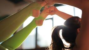 En härlig kvinnlig instruktör som gör asanas på matting i yogastudio arkivfilmer