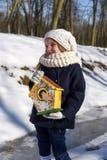 En härlig le liten flicka som rymmer ett fågelhus i en parkera royaltyfri fotografi