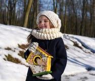 En härlig le liten flicka som rymmer ett fågelhus i en parkera royaltyfri foto